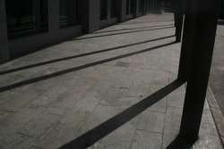 Covered cement walkway with columns casting dark shadows diagonally across the floor.