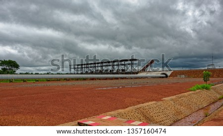 Covered conveyor belt mechanism transports bauxite ore, which is refined into aluminum, from an storage outside area to transhipment into a capesize bulk carrier ships in the Kamsar, Guinea, Africa.