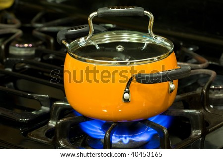 Covered non stick sauce pan on a stove top with fire is turned on