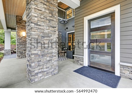Covered porch accented with stone column and modern glass front door. Northwest, UISA #564992470