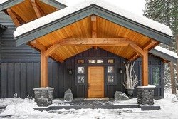 Covered Porch With Solid Wood Column And Natural Stone Pedestal Cover. Gray exterior of Beautiful modern contemporary home. Northwest, USA