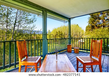 Covered porch with wooden table setting and nice forest landscape.  Northwest, USA #482377141