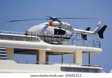 Covered silver helicopter on the deck of the yacht.