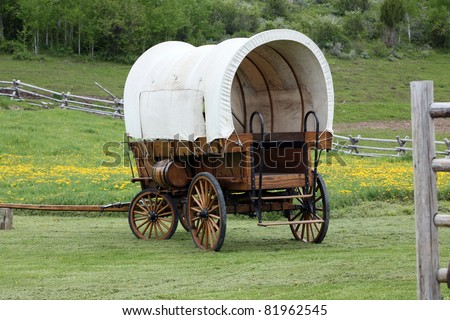 covered wagon in green field near trees and fence