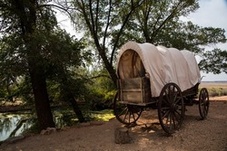 Covered wagon on a hill near a natural spring.  The wagon is ready to be hitched and be on its way across the prairie.