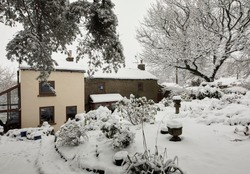 Covering the farmhouse, deep snow after daylong snowfall on moorland smallholding in Nidderdale.