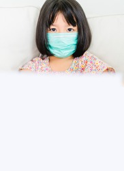 Covid-19 and Air pollution pm2.5 concept.Little chinese girl wearing mask for protect covid19 virus and show empty paper for use text for announcement.Covid-19 coronavirus and epidemic virus symptoms.