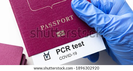 COVID-19 and travel concept, mark of coronavirus PCR testing in tourist passport. Diagnostics of coronavirus in airport due to lockdown. Business and tourism hit by corona virus during pandemic.