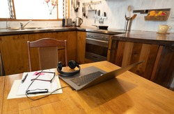 COVID-19 and working from home concept. Conceptual image with no people of workspace with laptop, headphones, glasses and paperwork on kitchen table in coronavirus pandemic and new normal.
