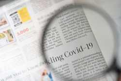 COVID-19 article on a newspaper through a magnifying glass. COVID-19 PANDEMIC. HEADLINES. NEWSPAPER.