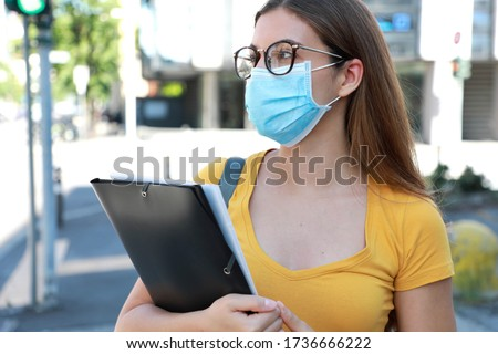 COVID-19 Beautiful University Student Female with Surgical Mask Walking in City Street. College Girl Back to School after Pandemic Coronavirus Disease 2019.