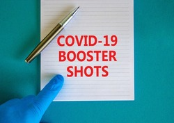 Covid-19 booster shots vaccine symbol. White note with words Covid-19 booster shots, beautiful blue background, doctor hand and metallic pen. Covid-19 booster shots vaccine concept.
