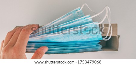 COVID-19 box of new surgical masks open package of PPE medical supplies for healthcare workers at hospital woman working in coronavirus pandemic taking a mask. Banner panoramic.