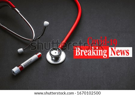 COVID 19 BREAKING NEWS text with stethoscope and blood sample vacuum tube on black background. Covid-19 or Coronavirus Concept