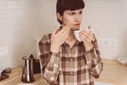COVID-19 causes loss of smell. Woman sniffing smell of coffee from cup while preparing drink in morning in kitchen. Female inhaling aroma of fresh beans. SARS-CoV-2 pandemic.