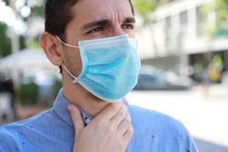 COVID-19 Close Up Man Wearing Surgical Mask with Sore Throat Outdoor. Portrait of Man with Face Mask Against SARS-CoV-2 Suffering Throat Pain in City Street.