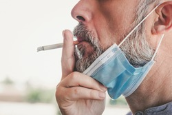 covid-19,Close-up of man with medical mask smoking a cigarette at the street background blur
