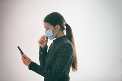 COVID-19 contact tracing app on mobile phone woman walking outside while wearing surgical medical mask touching her face texting smartphone, Coronavirus prevention with geolocation tracking app.