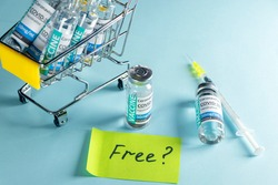 Covid-19 Corona Virus 2019-ncov vaccine vials medicine drug bottles in shopping trolley, syringe injection and note with text FREE . Vaccination, immunization, treatment to cure Corona Virus infection