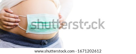 Covid19 coronavirus and pandemic virus symptoms.Close up of pregnant belly with surgical mask for protection tummy baby from Covid-19 virus or Coronavirus pandemic.Stop corona virus outbreak.isolated.