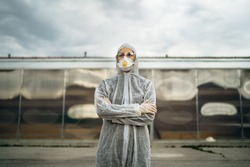 COVID-19 coronavirus doctor in hazmat suit.Infectious disease pandemic medical worker.Female physician in uniform on frontline,fighting viral outbreak.Protective suit with N95 mask.