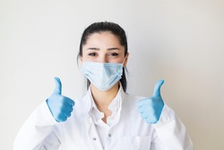 Covid19, coronavirus, healthcare and doctors concept. Portrait of optimistic female doctor assure everything be okay, thumb-up, wear medical mask to prevent catching virus, white coat