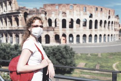 COVID-19 coronavirus in Europe, girl wearing face mask next to empty Colosseum, Rome, Italy. Tourist landmarks closed due to COVID19 corona virus pandemic.  Travel, tourism and lockdown concept.