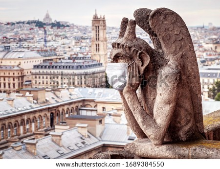 COVID-19 coronavirus in France, medical mask on gargoyle of Notre Dame in Paris. Tourist landmarks closed due to corona virus outbreak. Concept of travel, quarantine and COVID coronavirus pandemic.