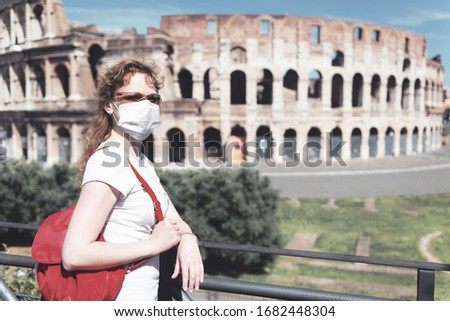 COVID-19 coronavirus in Italy, woman wearing face medical mask next to empty Colosseum, Rome. Tourist landmarks closed due to corona virus. COVID19 pandemic, quarantine, lockdown and travel concept.