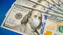 COVID-19 coronavirus in USA, 100 dollar money bill with face mask. Crisis and finance concept