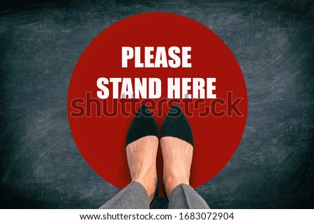 COVID-19 Coronavirus message asking supermarket customer to stand in space. Top view of feet standing in red circle with text in public space practicing social distancing. Blackboard background.