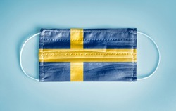 Covid-19 Coronavirus protection concept: Medical disposable face mask with Sweden flag on blue background.  WHO recommends usage of mask for prevention from Coronavirus.