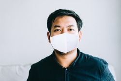 Covid-19 Coronvavirus.Working from home concept.Asian man wearing face mask ready for quarantine 14 day at home.Covid-19 virus outbreak.Working at home.Quarantine asian man.Pandemic virus symptoms.