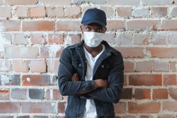 COVID, COVID-19, coronavirus, pandemic Young african black man wearing medical mask is standing in a cap with crossed arms shocked with coronavirus 2019 danger on background of ruined red brick wall