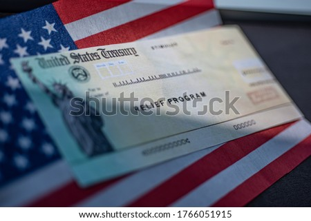 COVID-19 economic Stimulus check on blurred USA flag and sun light background. Relief program concept.