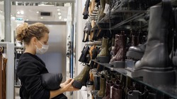 Covid-19 footwear shopping. Side view of white woman in face mask in boot shop