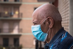 COVID-19 Headshot portrait of an old man wearing surgical mask looking outside from his balcony