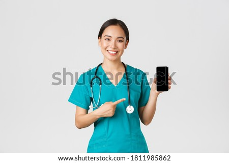 Covid-19, healthcare workers and online medicine concept. Smiling asian female doctor, physician in scrubs pointing finger at mobile screen, recommend download checkup, consultation application