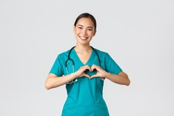 Covid-19, healthcare workers, pandemic concept. Lovely caring asian doctor, female nurse in scrubs showing heart gesture and smiling, taking care of patients with love, white background