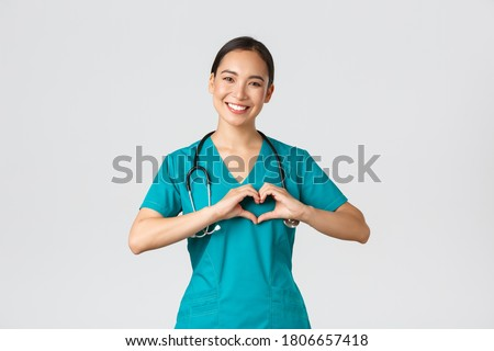 Covid-19, healthcare workers, pandemic concept. Lovely caring asian doctor, female nurse in scrubs showing heart gesture and smiling, taking care of patients with love, white background Foto stock ©