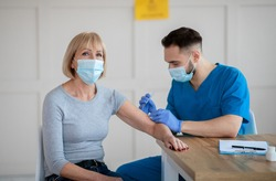 Covid-19 immunization concept. Senior Caucasian woman receiving intramuscular injection of coronavirus vaccine during doctor's appointment at clinic. Medical service and healthcare