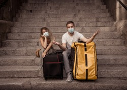 COVID-19 impact in international tourism. Sad tourist couple worried about coronavirus quarantine back home amid new travel regulations. Vacations cancellations due to coronavirus travel restrictions.