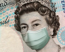 COVID-19 in UK, Close up of 5 British Pounds banknotes, with Queen Elisabeth II wearing healthcare surgical mask. Impact of the coronavirus pandemic on the UK economy. devaluation of the UK currency.