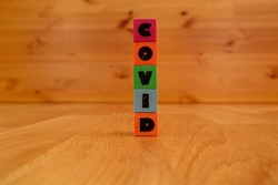 COVID inscription on worn plastic cubes on a wooden background. Covid-19 pandemic concept.