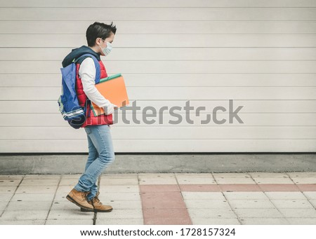 covid-19,kid with medical mask and backpack going to schooll outdoor Foto stock ©