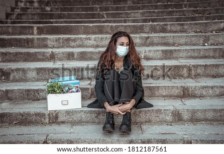 COVID-19 lay off and unemployment. Depressed business woman with face mask outside office with personal staff box feeling hopeless after losing job due to redundancy amid Coronavirus job cuts. Сток-фото ©
