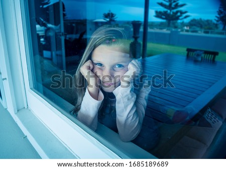 COVID-19 Lockdowns. Depressed and lonely little girl looking through the window during quarantine. Child feeling sad as coronavirusu pandemic forces families to stay home in self isolation.