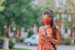 COVID-19 mask wear mandatory in city. Asian woman walking using mobile phone wearing face mask protection as prevention for coronavirus outside in city park summer lifestyle outdoor. Corona virus.