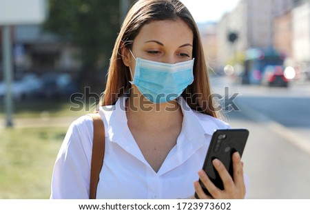 COVID-19 Mobile Application Young Woman Wearing Surgical Mask Using Smart Phone App in City Street to Aid Contact Tracing in Response to the 2019-20 Coronavirus Pandemic
