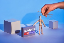 Covid19 novel coronavirus rumors. Sinister hand control wooden puppet on abstract geometric background. Box with text